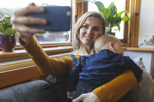 Woman taking a selfie with her cute sleeping son on the sofa - WPEF02493