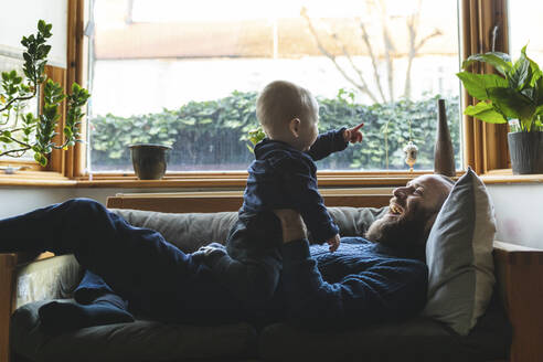Man playing with his little son on the sofa - WPEF02520