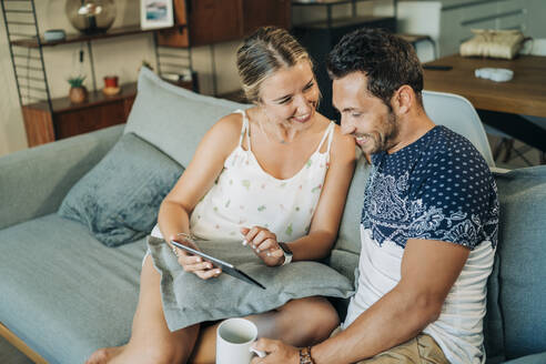 Happy relaxed couple sitting on couch in living room sharing a tablet - MPPF00460