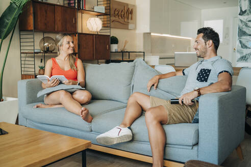 Happy couple sitting on couch in living room - MPPF00475