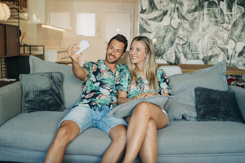 Happy couple sitting on couch in living room wearing Hawaiian shirts taking a selfie - MPPF00484