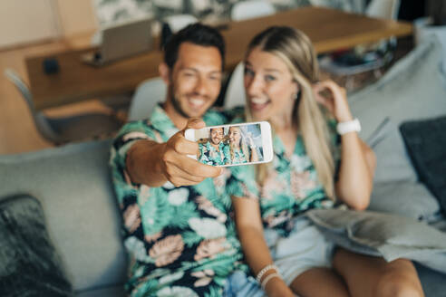 Happy couple sitting on couch in living room wearing Hawaiian shirts taking a selfie - MPPF00487