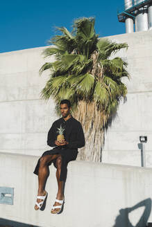 Young man wearing black kaftan holding a pineapple - AFVF05121