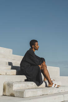 Young man wearing black kaftan sitting on concrete stairs under blue sky - AFVF05151