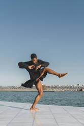 Young man wearing black kaftan performing at the waterfront - AFVF05199