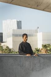 Young man wearing black kaftan behind a concrete wall - AFVF05202