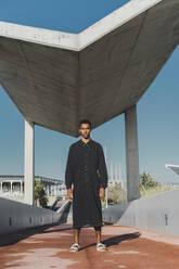 Young man wearing black kaftan standing on a footbridge - AFVF05205