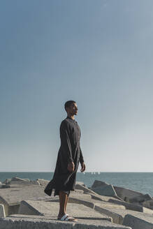 Young man standing at the coast wearing black kaftan - AFVF05208