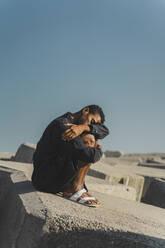 Young man wearing black kaftan sitting on concrete blocks under blue sky - AFVF05214