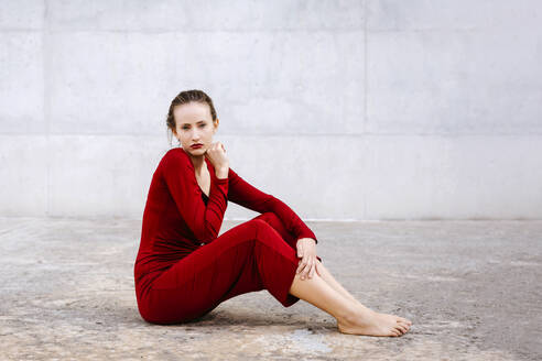 Portrait of pretty barefoot woman in red dress sitting on urban floor - TCEF00075