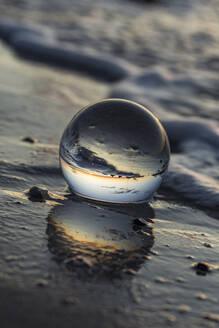 Germany, Mecklenburg-West Pomerania, Prerow, Shiny glass ball lying in wet beach sand - STBF00530