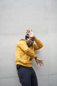 Mature man wearing mirrored sunglasses and yellow jacket raising hands - AFVF05263