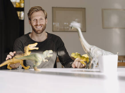 Portrait of smiling man with toy dinosaurs on table - KNSF07001