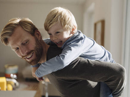 Happy father carrying son piggyback at home - KNSF07016