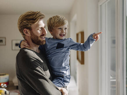 Happy father carrying son at home - KNSF07019