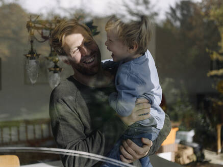 Happy father carrying son at the window at home - KNSF07022