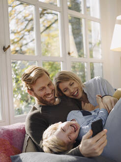 Happy family using cell phone in sunroom at home - KNSF07031