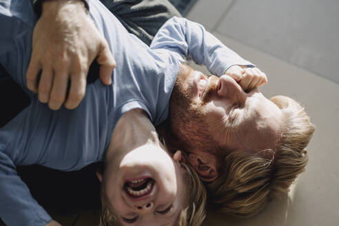 Happy father and son cuddling on the floor at home - KNSF07070