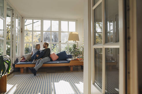 Affectionate couple relaxing in sunroom at home - KNSF07082