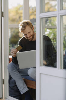 Smiling man using laptop and credit card in sunroom at home - KNSF07088