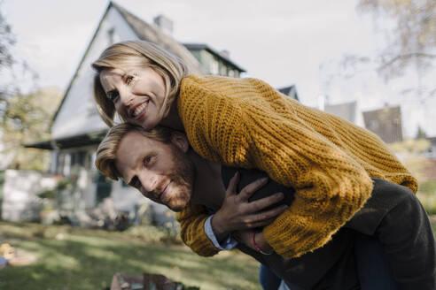 Man giving his wife a piggyback ride in garden - KNSF07097