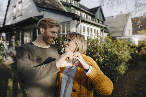 Smiling couple standing in front of their home shaping a heart with their hands - KNSF07103