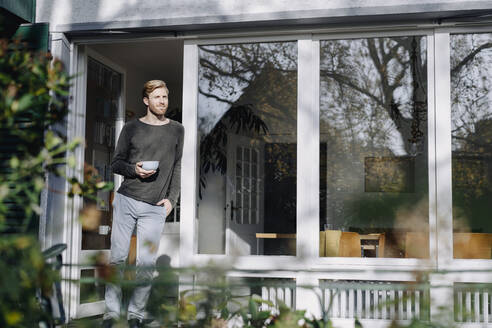 Man in sunroom at home leaning against the window - KNSF07118