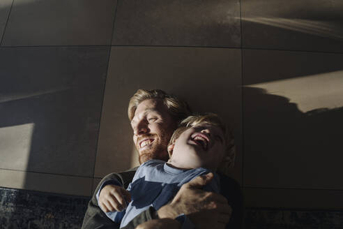 Happy father and son cuddling on the floor at home - KNSF07124
