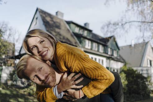 Man giving his wife a piggyback ride in garden - KNSF07133
