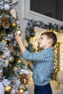 Boy watching Christmas bauble at tree - EYAF00901