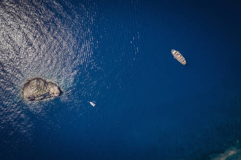 Italy, Province of Livorno, Elba, Aerial view of boats floating in blue waters of Mediterranean Sea - DHEF00044