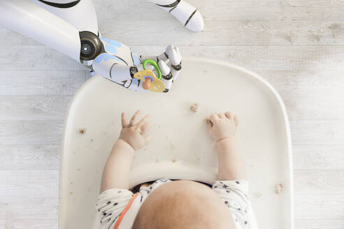 Robot hand giving pacifier to baby boy sitting in high chair playing with bread crumps, top view - KSHSF00020