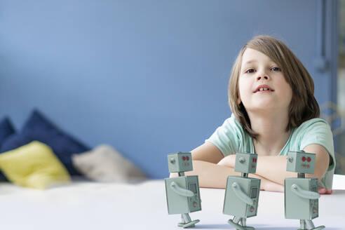 Portrait of boy with three toy robots - KSHSF00023