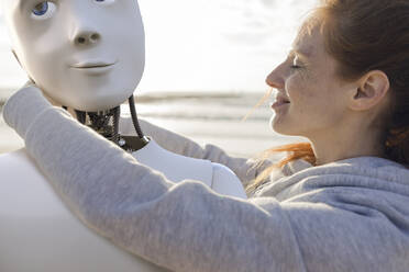 Happy woman embracing robot on the beach - KSHSF00026