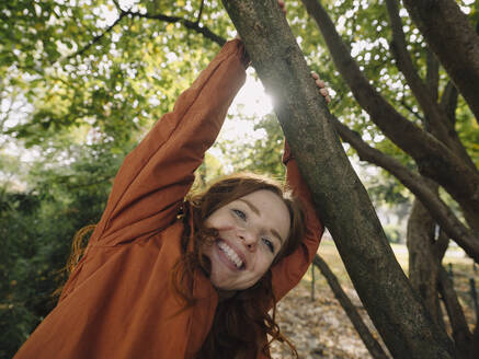 Happy redheaded woman enjoying autumn in a park - KNSF07154
