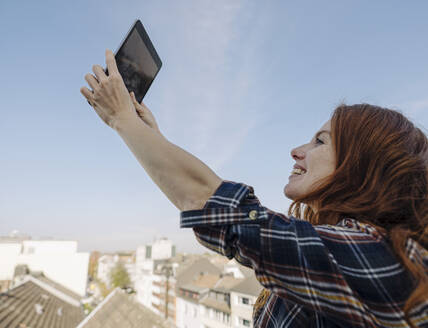 Smiling redheaded woman with tablet on rooftop terrace taking a selfie - KNSF07163