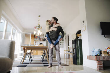 Man carrying happy woman piggyback in their comfortable home - KNSF07212