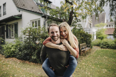 Man carrying happy woman piggyback in garden - KNSF07218
