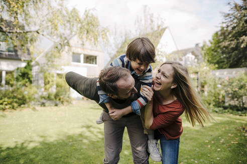 Parents and son having fun, playing in the garden - KNSF07239