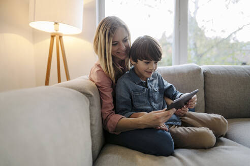 Mother and son sitting on couch, using digital tablet - KNSF07260