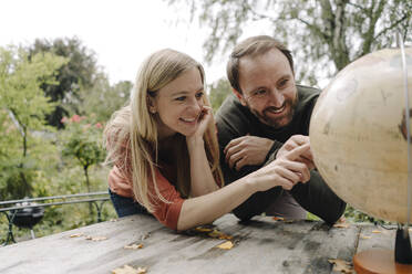 Happy couple planning to travel, looking at globe outdoors - KNSF07302