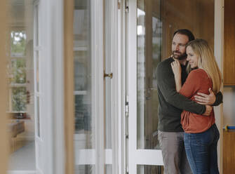 Happy couple embracing in their comfortable home - KNSF07308