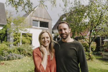 Happy couple standing in their garden - KNSF07314