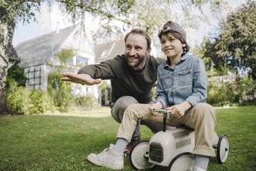 Father and son playing with toy car in the garden - KNSF07329