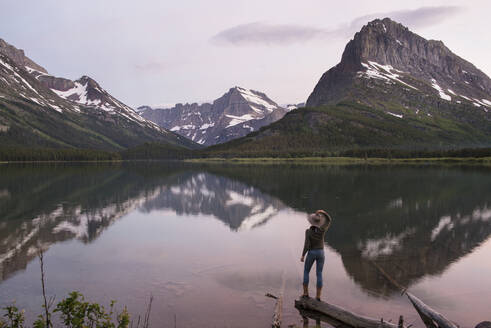Rear view of hiker looking at Mt. Grinnell while standing on wood by Swiftcurrent Lake - CAVF73559