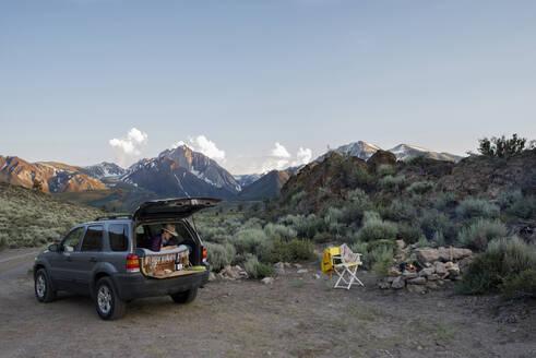 Female hiker sitting in sports utility vehicle against Mount Morrison - CAVF73568