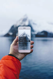 Close-up of tourist taking a smartphone picture at Hamnoy, Lofoten, Norway - DGOF00064