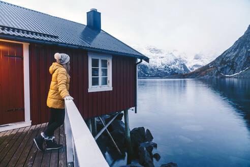 Tourist enjoying the view at Hamnoy, Lofoten, Norway - DGOF00073