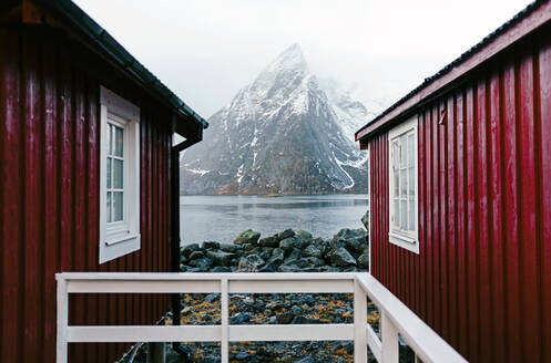 Red huts and snowcapped mountain at the coast, Hamnoy, Lofoten, Norway - DGOF00121