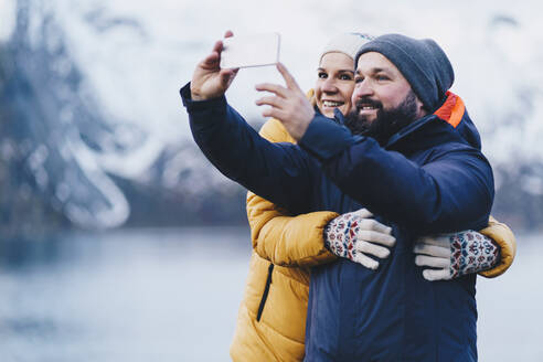 Tourist couple taking a selfie at Hamnoy, Lofoten, Norway - DGOF00142